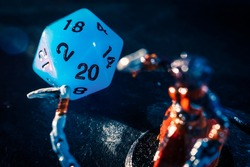 Close-up of a blue twenty sided dice and a role playing mini on a dark surface. Focused on the Dice . Lens flare