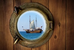 Close-up of a boat closed porthole with view to an old galleon