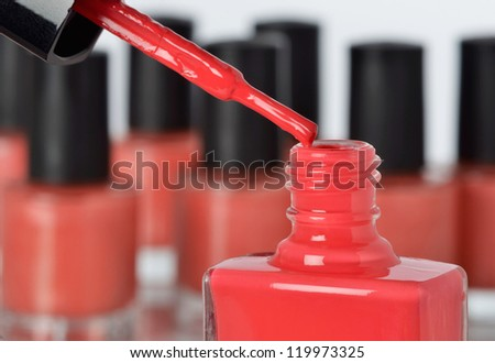 Close-up of a bottle of red nail polish with other bottles in background