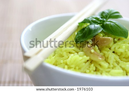 Close up of a bowl of fragrant yellow rice with lentil, cumin and cashew nuts garnish with a sprig of basil leaf and a pair of chopstick. Narrow Depth Of Field.