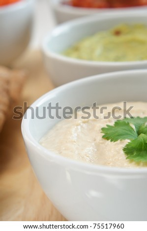 Close up of a bowl of hummus with guacamole and salsa dips in the background.  Pitta bread just visible at left frame.