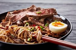 close-up of a bowl of soba noodles with sliced roast beef steak, shiitake mushrooms, half of hard boiled egg and fried vegetables with chopsticks, asian cuisine, view from above, macro