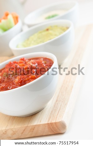 Close up of a bowl of tomato salsa, with guacamole, hummus dips and crudites in the background.