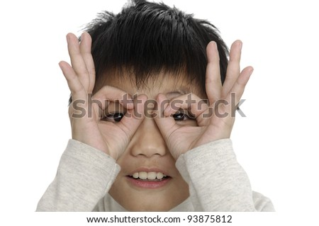 Close-up of a boy making faces playing with his hands