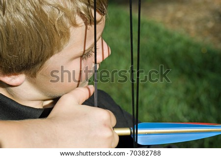 Close up of a boy ready to pull the bow to shoot and arrow.