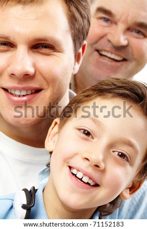Close-up of a boy?s face looking at camera among his father and grandfather