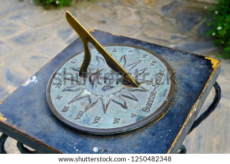 Close-up of a brass sundial mounted on a stone plinth in a garden, Sundial in the Summer sun. #1250482348