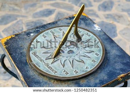 Close-up of a brass sundial mounted on a stone plinth in a garden, Sundial in the Summer sun. #1250482351