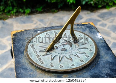 Close-up of a brass sundial mounted on a stone plinth in a garden, Sundial in the Summer sun. #1250482354