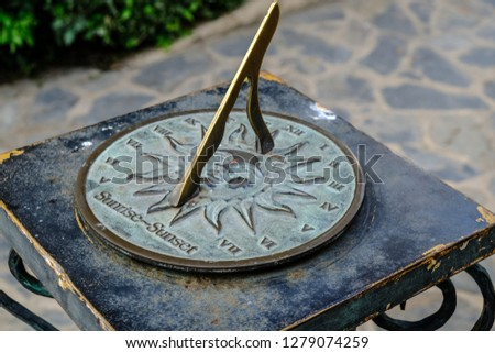 Close-up of a brass sundial mounted on a stone plinth in a garden, Sundial in the Summer sun. #1279074259