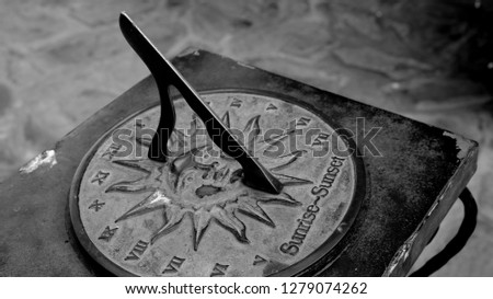 Close-up of a brass sundial mounted on a stone plinth in a garden, Sundial in the Summer sun. #1279074262