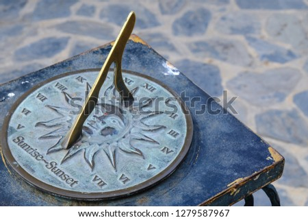 Close-up of a brass sundial mounted on a stone plinth in a garden, Sundial in the Summer sun. #1279587967