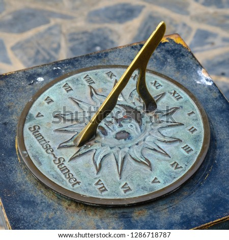 Close-up of a brass sundial mounted on a stone plinth in a garden, Sundial in the Summer sun. #1286718787