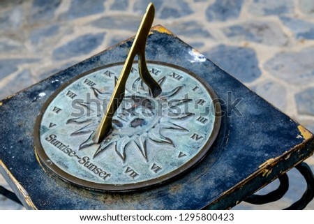 Close-up of a brass sundial mounted on a stone plinth in a garden, Sundial in the Summer sun. #1295800423
