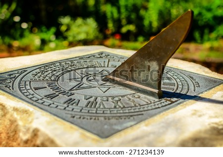 Close-up of a brass sundial mounted on a stone plinth in Wellington Botanic Garden, New Zealand. Soft selective focus and shallow depth of field #271234139