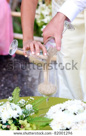 Close-up of a bride and groom during a sand pouring ceremony.