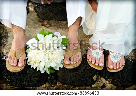 Close up of a bride and groom's feet and bouquet. They had just gotten married on the beach and are wearing sandals.