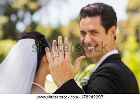 Close-up of a bridegroom showing his wedding ring to the camera in the park #178949207