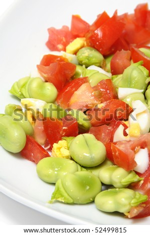 close up of a broad beans salad with tomato and boiled egg