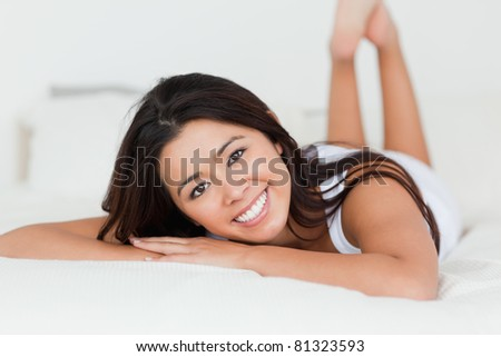 close up of a brunette woman lying on bed in bedroom with crossed legs