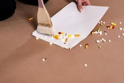 Close-up of a brush collecting colored pills on a white sheet of paper. The concept of disposing of expired medicines or violation of integrity.