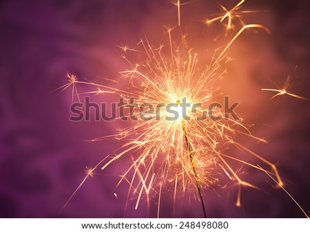Close up of a burning sparkler on a vibrant background