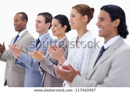 Close-up of a business team smiling and applauding with focus on the last three people against white background