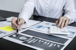 Close-up of a business woman holding a pen and pointing at a financial data sheet and pressing a calculator, she is checking monthly financial documents from the finance department. Financial concept.