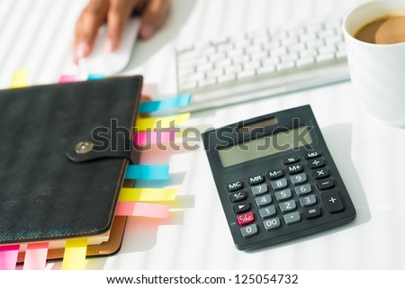 Close-up of a business workplace with an organizer, a calculator and a cup of coffee