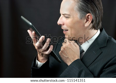 Close-up of a businessman admiring his tablet.