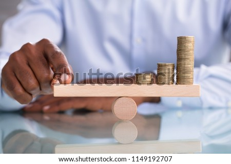Close-up Of A Businessman Balancing The Coin Stack On Wooden Seesaw Over The Reflective Desk