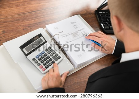 Close-up Of A Businessman Calculating Invoice Using Calculator At Desk In Office