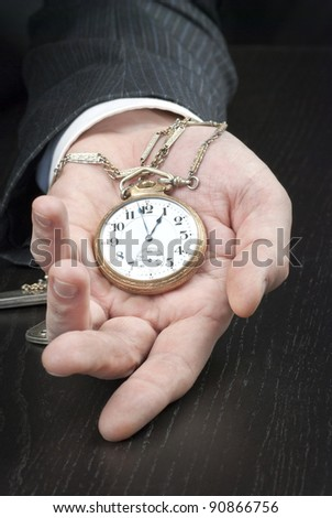 Close-up of a businessman displaying an open pocket-watch in his hand.