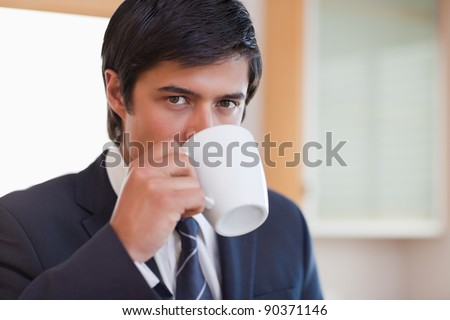 Close up of a businessman drinking coffee in his kitchen
