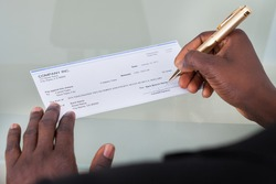Close-up Of A Businessman Filling Blank Cheque