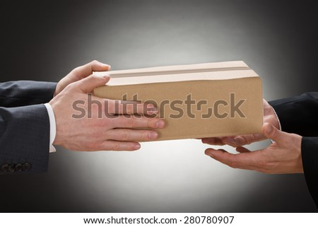 Close-up Of A Businessman Giving Box To His Colleague