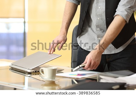 Close up of a businessman hands leaving work and closing laptop at office