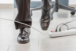 Close up of a businessman legs stumbling with an electrical cord at office