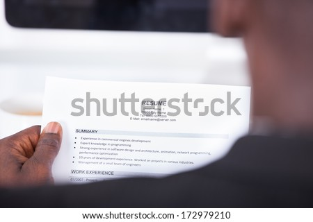 Close-up Of A Businessman Looking At Resume Holding In Hand