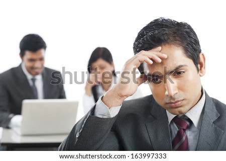 Close-up of a businessman looking upset with his colleagues in the background Photo stock ©