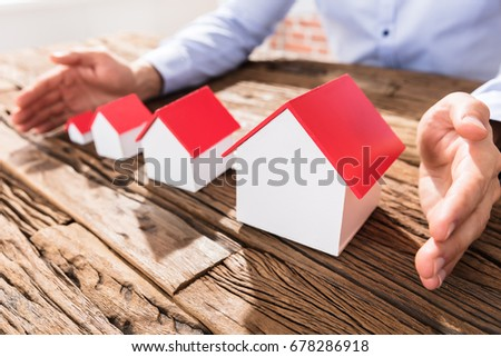 Close-up Of A Businessman Protecting The Scales Of House Models With Hands
