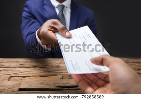 Close-up Of A Businessman's Hand Giving Cheque To Colleague Over Wooden Desk #792858589