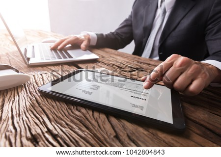 Close-up Of A Businessman's Hand Working With Invoice On Digital Tablet
