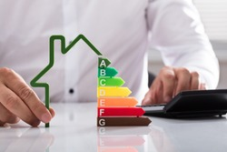 Close-up of a businessman using calculator holding outline of house model with energy efficiency rate