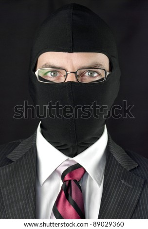 Close-up of a businessman wearing a balaclava looking at camera