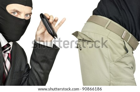 Close-up of a businessman wearing a balaclava picking the trouser pocket of a middle class man.
