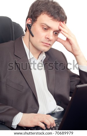 Close Up of a businessman with headset. He is working on laptop