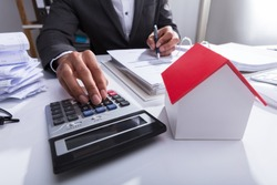 Close-up Of A Businessperson Calculating Bill With House Model On Desk