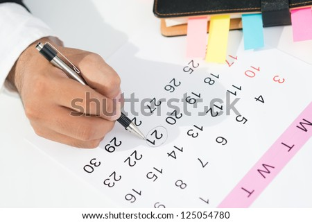 Close-up of a businessperson making an appointment in the calendar