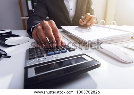 Close-up Of A Businessperson's Hand Calculating Bill With Calculator